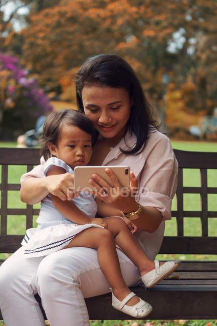 Lindo asiático madre y hija usando smartphone en banco - foto de stock