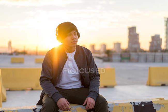 Молодой азиат, наслаждающийся закатом в наушниках — стоковое фото