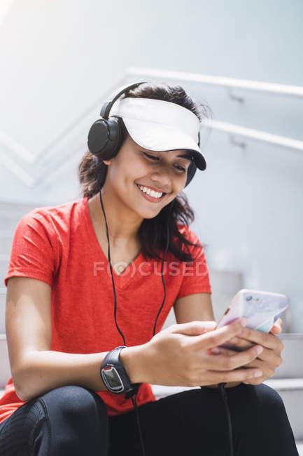 Joven asiático deportivo mujer usando auriculares y elegante - foto de stock