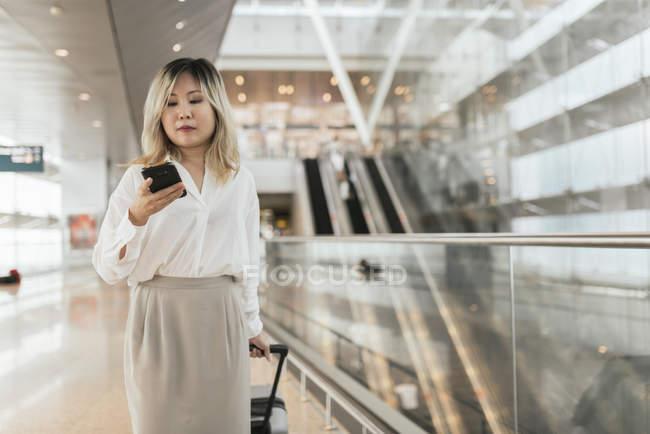 Joven exitosa mujer de negocios con smartphone en el aeropuerto - foto de stock