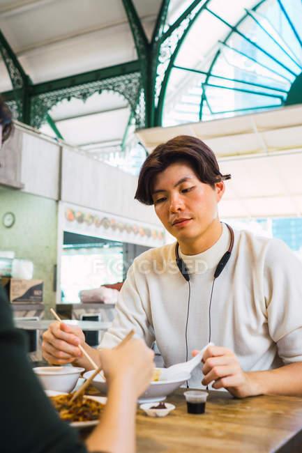 Junge asiatische paar gemeinsames Essen im café — Stockfoto