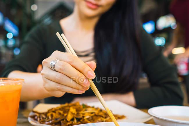 Junge Asiatin, Essen mit Stäbchen — Stockfoto