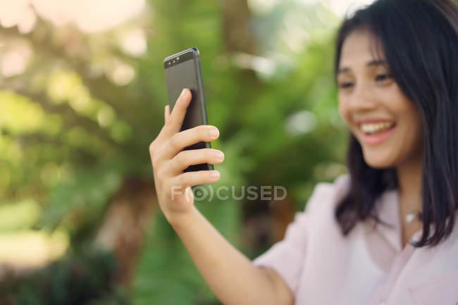 Feliz asiático mujer tomando selfie en parque - foto de stock