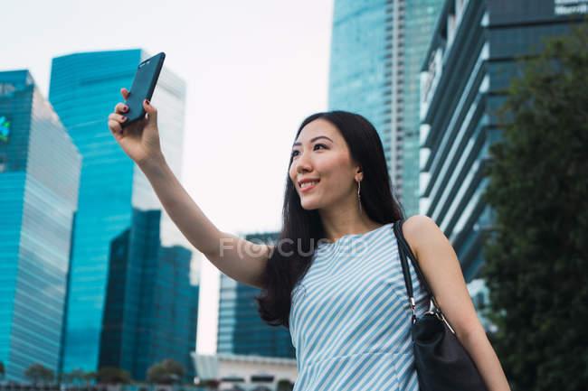 Joven asiático mujer tomando selfie en ciudad calle - foto de stock