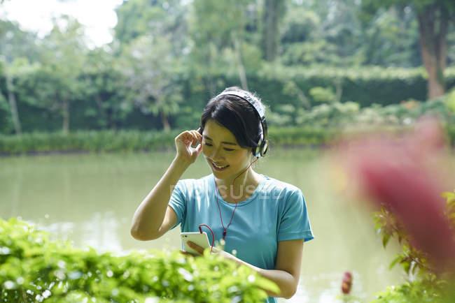 Porträt einer Frau, die beim Spazierengehen im botanischen Garten Musik hört — Stockfoto