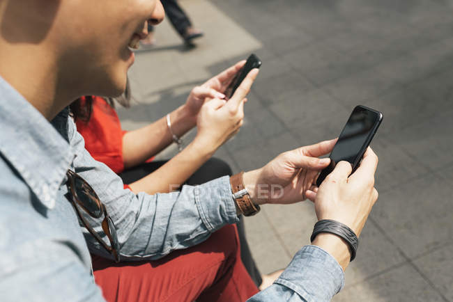 Couple de chinois asiatiques à l'aide de téléphones cellulaires à Chinatown — Photo de stock