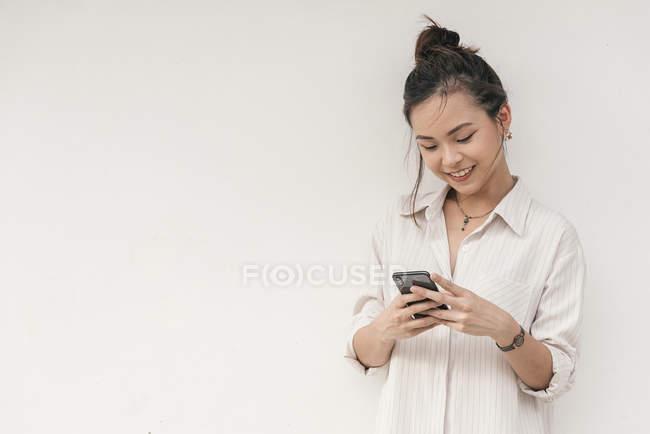 Молоді азіатські жінки з усмішкою, за допомогою смартфона — стокове фото