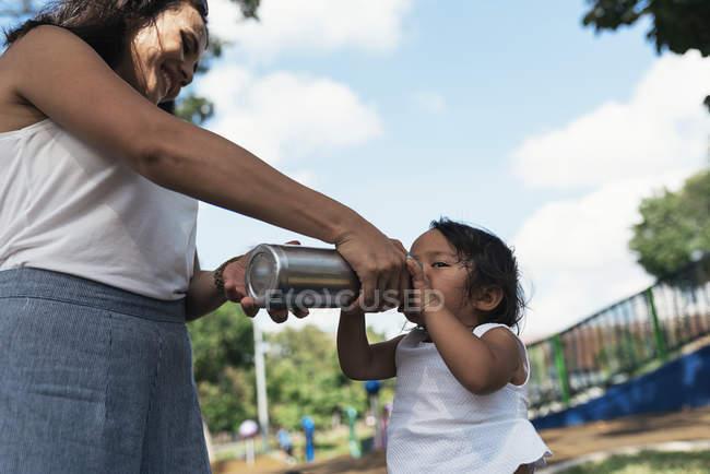 Молодая мать дает азиатской дочери пить из термоса бутылку — стоковое фото
