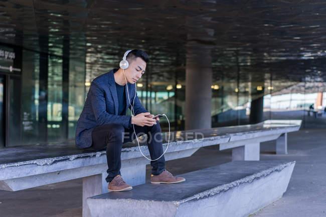 Jovem asiático homem usando fone de ouvido e smartphone na cidade — Fotografia de Stock