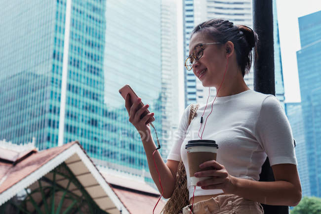 Young attractive asian woman using smartphone and holding coffee — Stock Photo