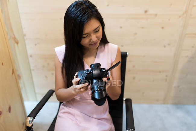 Young asian successful businesswoman with camera in modern office — Stock Photo