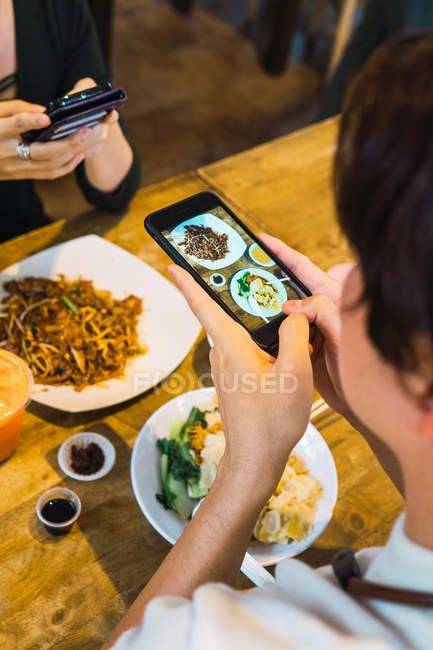 Young asian couple taking food photo in cafe — Stock Photo