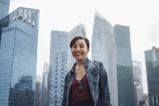 Giovane signora di Singapore che sorride alla telecamera e posa con i grattacieli a Singapore . — Foto stock