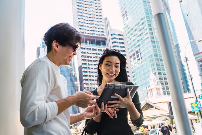 Young asian couple sharing tablet in city — Stock Photo
