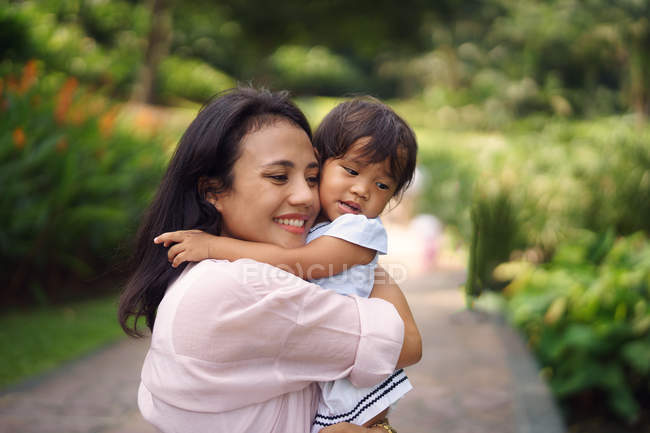 Cute asian mother and daughter hugging in park — Stock Photo