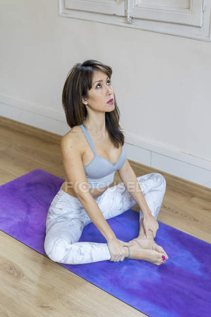 Young asian woman sitting on mat and looking upwards — Stock Photo