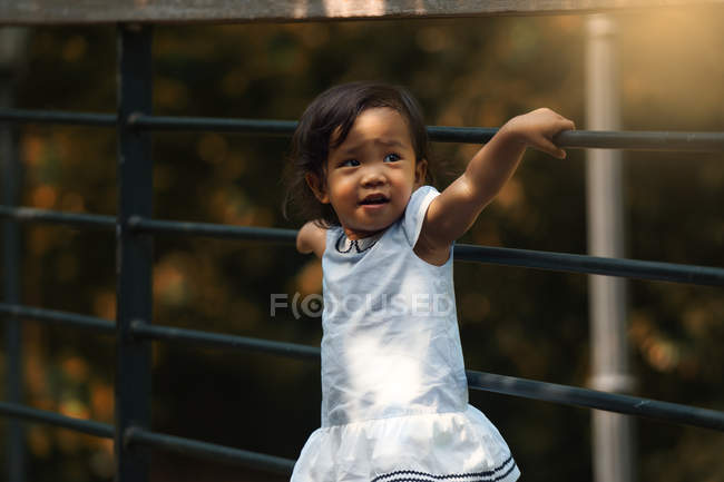 Little cute asian girl beside fence at park — Stock Photo