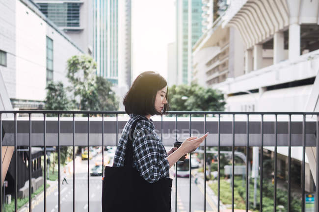 Young beautiful asian girl in casual clothes using smartphone on city streets — Stock Photo