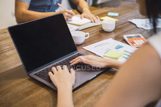 Cropped image of woman working with laptop in creative modern office — Stock Photo