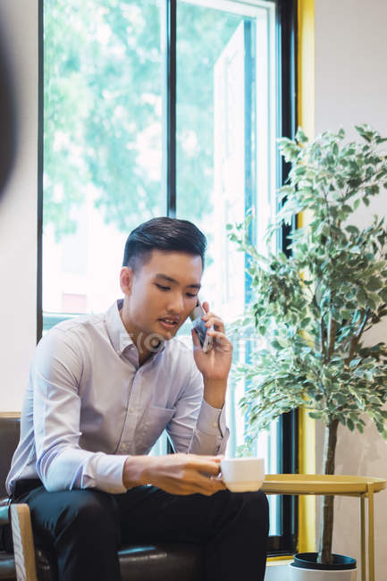Young asian man with coffee smart — Stock Photo