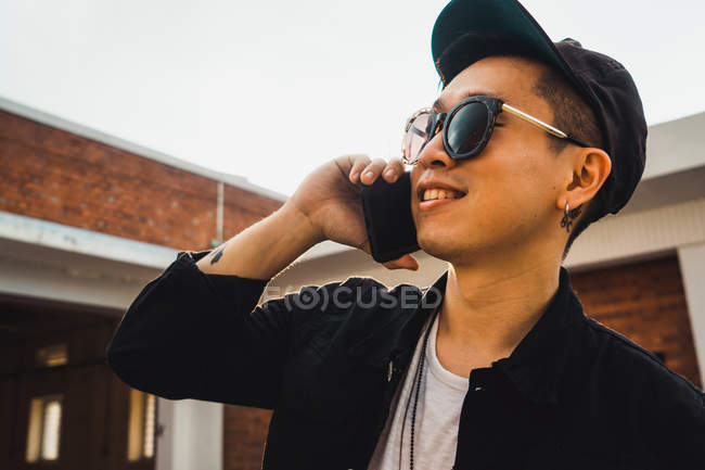 Cool young asian man using smartphone outdoors — Stock Photo