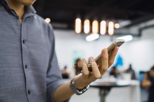 Cropped image de l'homme à l'aide de smartphone au bureau — Photo de stock