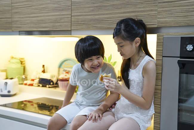 Siblings sharing a bun in the kitchn — Stock Photo