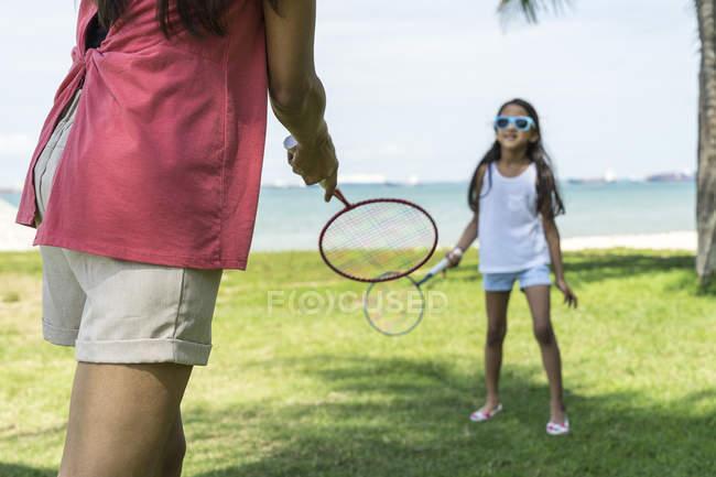 Madre e figlia giocare badminton sulla spiaggia — Foto stock
