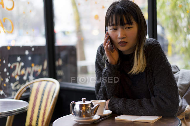 Young attractive casual asian woman with smartphone in cafe — Stock Photo