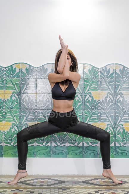 Junge asiatische Frau tut Adler Pose über Matte — Stockfoto