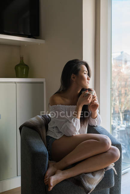 Young Chinese woman on a sofa drinking — Stock Photo