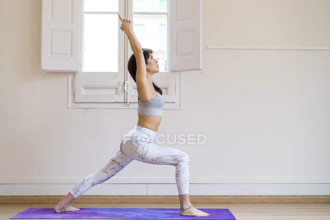 Young asian woman doing warrior one pose — Stock Photo