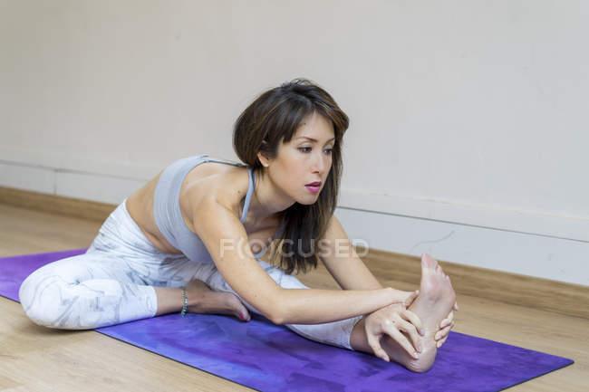 Молодая азиатка делает упражнения на растяжку на коврике — стоковое фото
