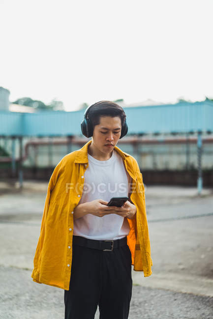 Cool jovem asiático homem usando smartphone ao ar livre — Fotografia de Stock