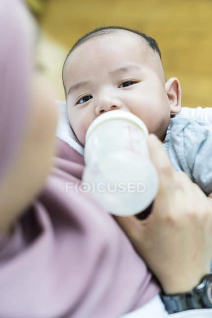 Азиатская мусульманская мать кормит своего ребенка молоком . — стоковое фото