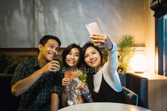 Giovani amici asiatici prendendo selfie in confortevole bar — Foto stock