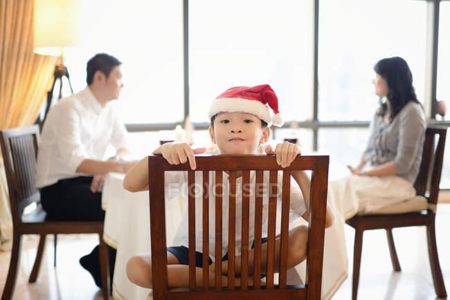 Famiglia asiatica felice alle vacanze di Natale, ragazzo che si siede sulla sedia in cappello della santa — Foto stock