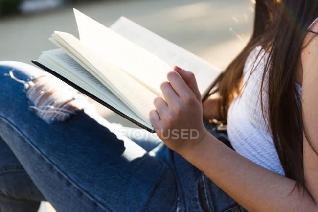 Обрезанный образ молодой евразийской женщины, читающей книгу — стоковое фото