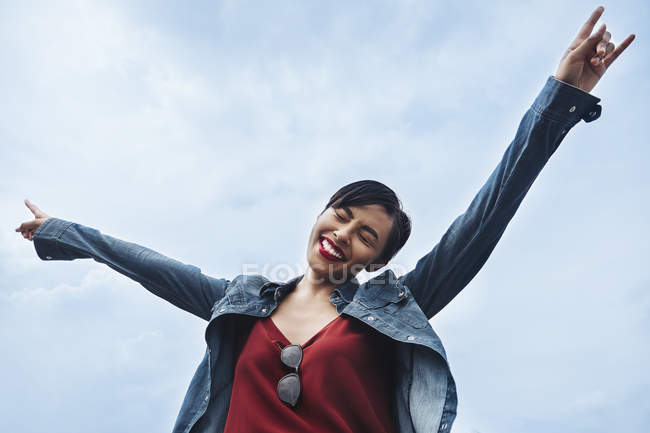 A happy and cheerful young Malay lady in Singapore throwing her hands in the air and smiling. — Stock Photo