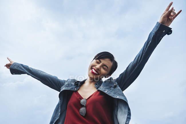 Uma jovem malaia feliz e alegre em Cingapura jogando as mãos no ar e sorrindo . — Fotografia de Stock