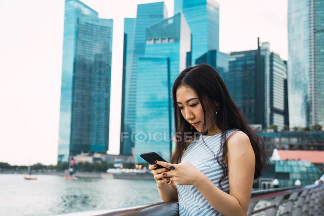 Joven asiático mujer usando smartphone contra rascacielos - foto de stock