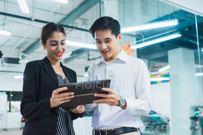 Young asian business people using tablet in modern office — Stock Photo