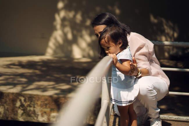 Мило азиатских мать и дочь, выглянув перила в парке — стоковое фото