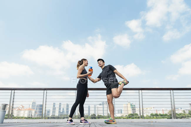 Happy asian sporty couple together, man making stretching — Stock Photo