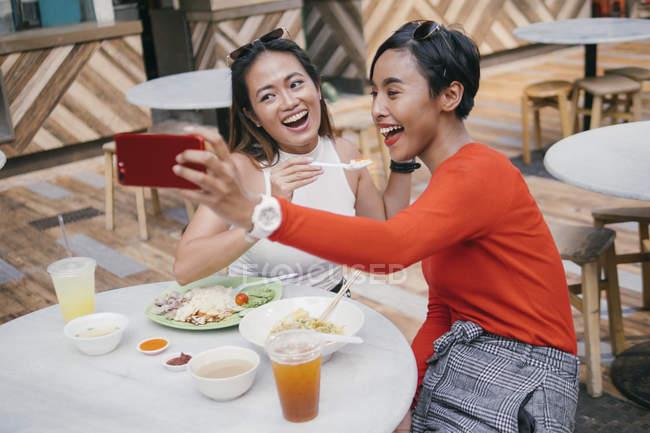 Giovani asiatiche amiche di sesso femminile prendendo selfie a food court — Foto stock