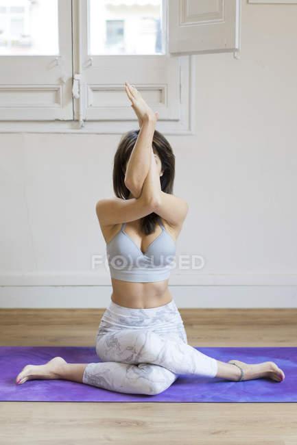 Young asian woman doing yoga on mat — Stock Photo