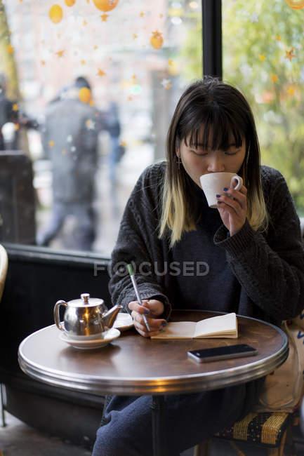 Giovane attraente casuale asiatico donna bere caffè e scrittura note in caffè — Foto stock