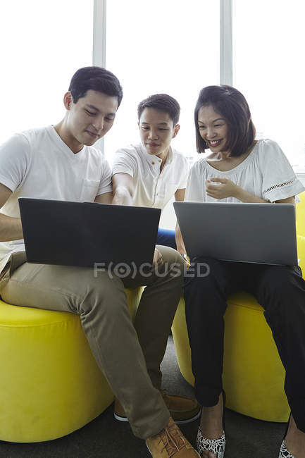 Young asian business people working with laptops at modern office — Stock Photo