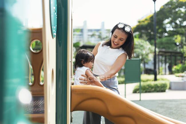 Молодая мать с азиатской дочерью на детской площадке — стоковое фото