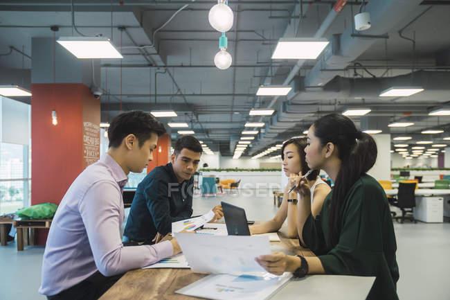 Молодые азиатские бизнесмены на встрече в современном офисе — стоковое фото